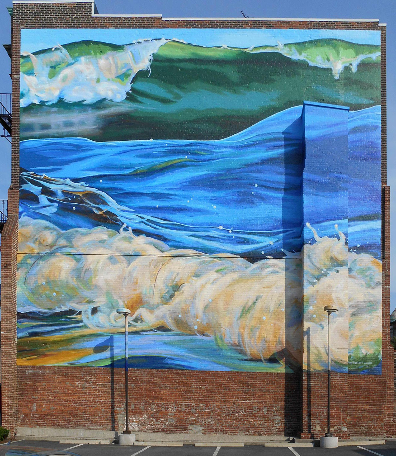 mural showing three ocean waves painted on a brick wall